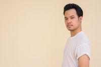 Portrait of Asian man wearing white t-shirt against plain background outdoors