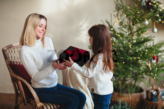 Cute girl daughter giving Christmas gift her young smiling mother while celebrating New Year at home