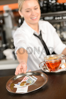 Attractive waitress taking tip in bar EUR