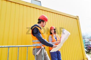 Architektin und Handwerker schauen auf einen Bauplan