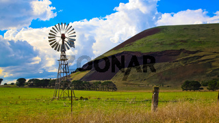 Windmill on a farm with volcanic mountain in the background