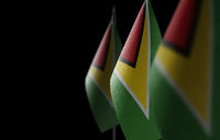 Small national flags of the Guyana on a black background