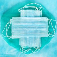 Group of antiviral protective face masks on blue medical background