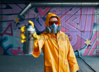 Graffiti artist pointing spray paint can to camera
