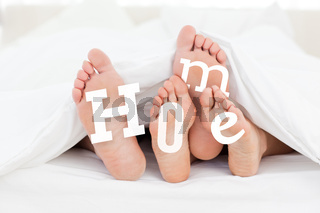 Pair of feet under the duvet with home text