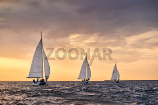 Russia, St.Petersburg, 05 September 2020: Some sailboats in a list goes by sea, the sky of pink color, the storm sky, regatta