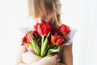 Smiling small girl holding and sniffing bouquet of red tulips. Greeting card