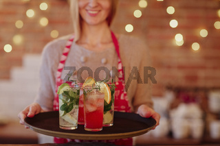 Smiling waitress in colored apron holding tray with alcoholic drinks and various cocktails