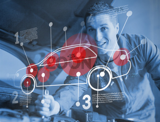 Mechanic reparing car while consulting futuristic interface