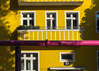 Yellow apartment building with a balcony and a pink water pipe