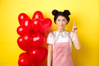 Valentines day concept. Beautiful korean girl dreaming of perfect date, making wish and looking at upper left corner, standing near red hearts balloons, yellow background