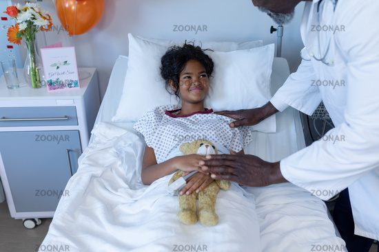 African american male doctor reassuring smiling sick mixed race girl in hospital bed holding teddy