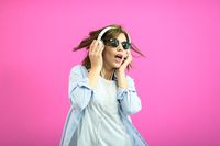 brunette lady in black glasses dancing and listening music isolate on pink background