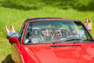 Smiling young couple relaxing in classy cabriolet