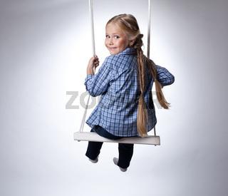 Pretty girl sitting on swing