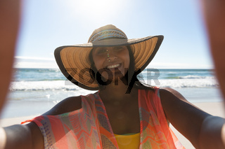 Smiling mixed race woman on beach holiday taking selfie