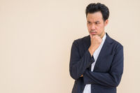 Serious Asian businessman thinking with hand on chin
