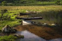 Sunken paddle boats in Lough Gummeenduff in beautiful Black Valley at sunset
