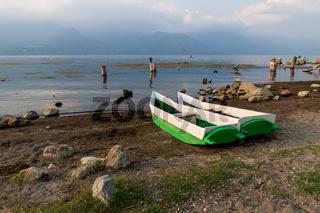 Two local fishermen canoes at the shore along lake Atitlan during sunset in San Pedro la Laguna, Guatemala