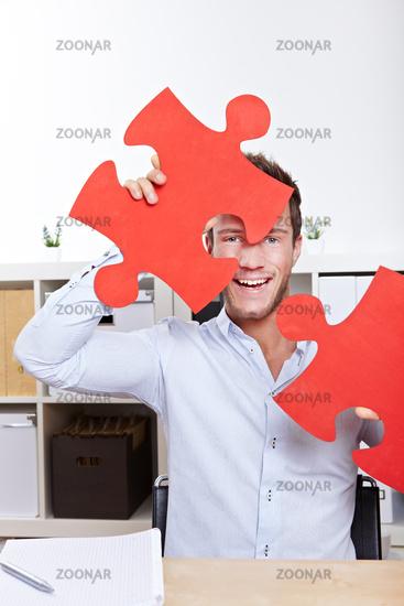 Lachender Mann mit Puzzleteilen