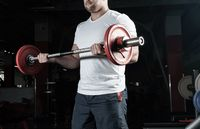 Male athlete lifts the barbell