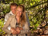 Glückliches Paar eng umschlungen mit Herbstwald im Hintergrund