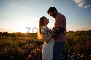 Embracing couple in rays of setting sun
