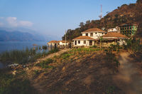 Coast at lake Atitlan with garden and sunlit houses, San Juan la Laguna, Guatemala