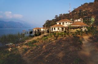 Coast at lake Atitlan with garden and sunlit houses, San Juan la Laguna, Guatemala