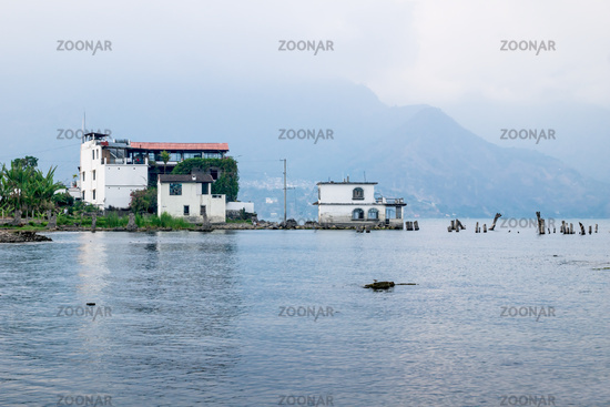 House at the coast of lake Atitlan along misty mountains, San Pedro la Laguna, Guatemala