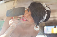 a beautiful retro-looking girl with blue eyes and red lips through the windscreen