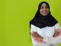 african muslim woman wearing hijab and traditional muslim clothes posing in front of green background