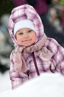 Cute baby is smiling outdoor snow winter. Christmas time