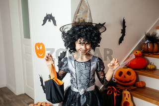 Adorable girl posing in pink dress and witch hat