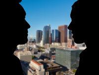 Zwei Geschäftsleute im Profil vor Los Angeles Skyline