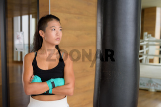 Asian woman kick boxer ready for exercise at gym and thinking