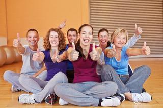 Gruppe im Fitnesscenter hält Daumen hoch