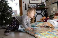 kleines Mädchen betrachtet auf dem Boden des Wohnzimmers ein großes Bilderbuch