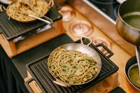 A close-up of a frying pan with spaghetti on a cast iron stove in the kitchen during cooking.