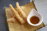 Three Shrimps tempura with sauce on yellow bamboo plate