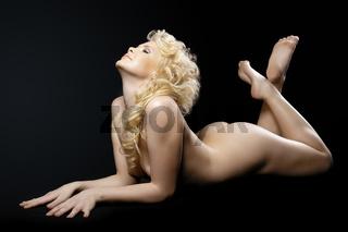 bare  woman lay on dark