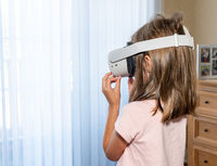 Young girl watching an app on a modern VR headset