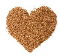 heap of uncooked buckwheat grains, top view. Groats laid out in the shape of a heart