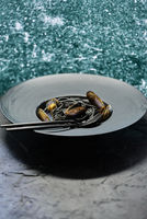 Seafood black spaghetti pasta with clams served on black plate on dark stone