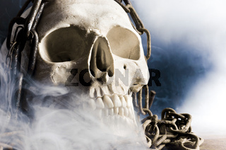 human skull with chain and smoke