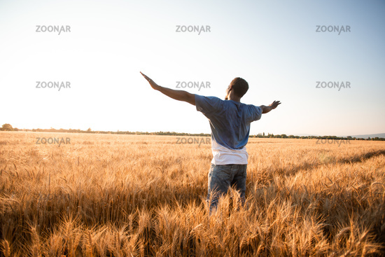 Unspecified man with hands up watching sunset