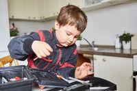 Junge sucht Werkzeug in der Werkzeugkiste