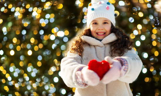 happy little girl with heart over christmas tree