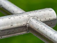 Rain drops on a gray metallic construction  of chrome bars