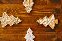 Four gingerbread cookies in the shape of Christmas trees. Arrows pointing to the center.